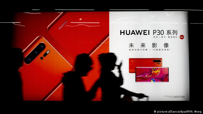People walk in front of a Huawei P30 smartphone ad