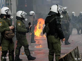 Police in the street as petrol bomb burns in the background