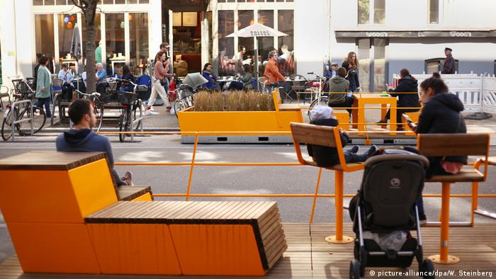 Auf gelben Bänken und Stühlen sitzen Leute an einer Straße
