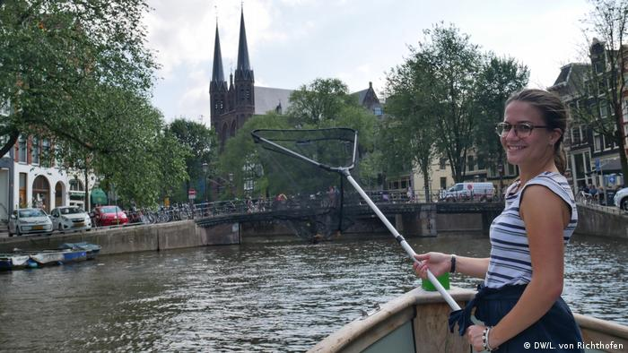 DW Reporter Giulia Saudelli in Amsterdam, fishing plastic waste out of the canals.