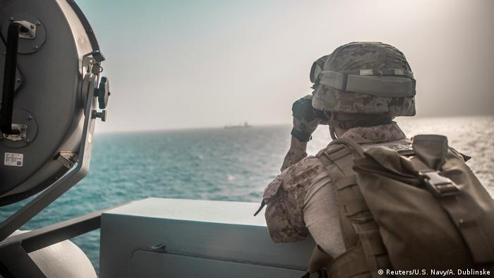 A US soldier observes a nearby boat while transiting through the Strait of Hormuz