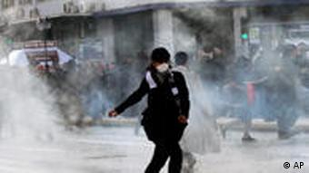 A demonstrator runs away from tear gas, in central Athens