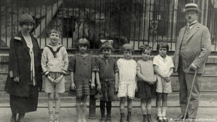 A family in front of the tigers' cage, ca. 1920