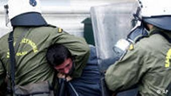 Riot police arrest a protester during clashes in Athens