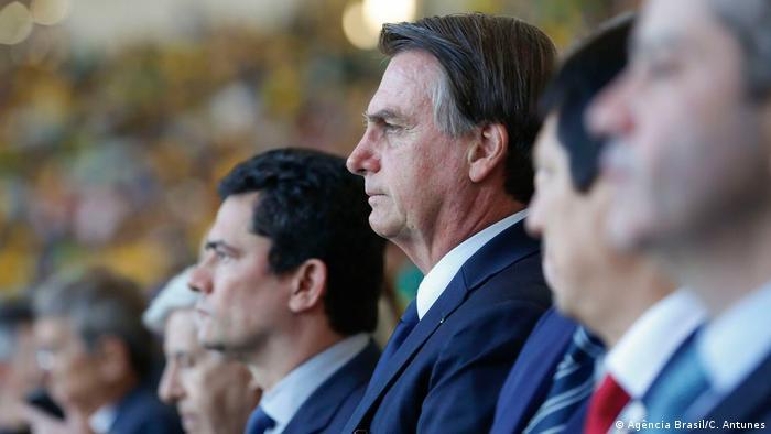 O ex-ministro da Justiça Sergio Moro ao fundo, ao lado do presidente Jair Bolsonaro