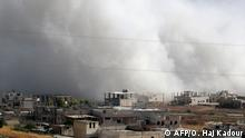 July 19, 2019*** TOPSHOT - Smoke billows above buildings during a reported air strike by pro-regime forces on Khan Sheikhun in the Syria's Idlib province on July 19, 2019. - Russian and Syrian regime aircraft have ramped up strikes on Idlib since late April, killing more than 600 civilians and wounding scores of others, according to the Britain-based Observatory, which relies on a network of sources inside Syria (Photo by Omar HAJ KADOUR / AFP)