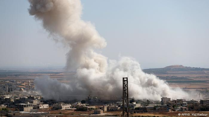 Smoke billows after an attack by pro-regime forces in Idlib province, Syria