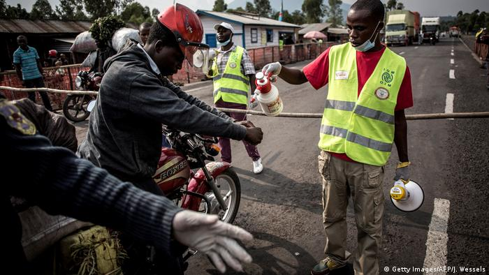 An aid worker sprays the hands of a motor cycle rider with water (Getty Images/AFP/J. Wessels)