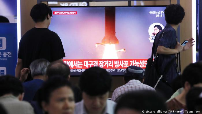 People watch a TV showing a file image of North Korea's missile launch during a news program at the Seoul Railway Station in Seoul