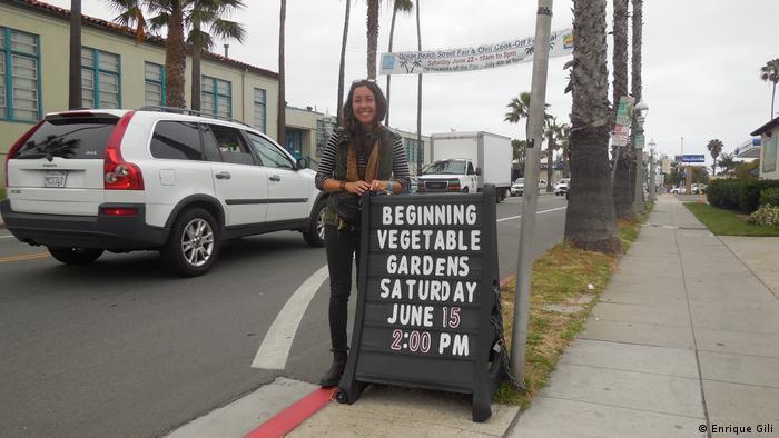 Bibliotheksmitarbeiterin Destiny Rivera steht neben einem Schild des örtlichen Gemeinschaftsgartens