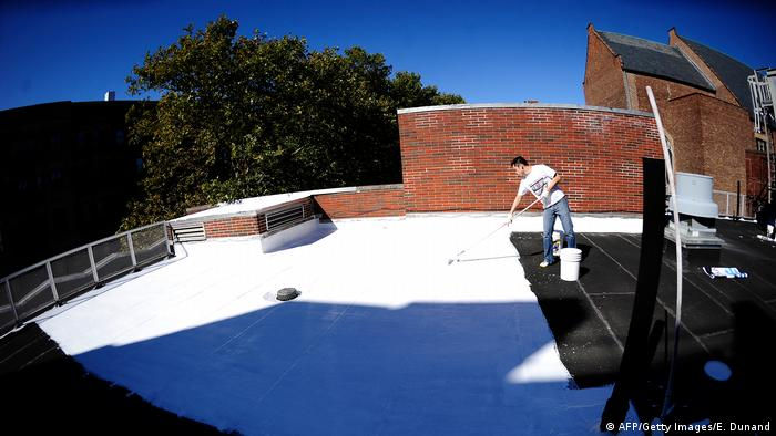 Volunteer in New York paints the roof of a school with a special white paint that reflects 80% of sunlight