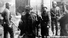 ARCHIV - Zwei Juden, die sich in einem Haus versteckt hatten, werden von SS-Soldaten gefangen genommen. Die Aufnahme entstand während des Warschauer Ghetto-Aufstands, der vom 19. April 1943 bis zu seiner blutigen Niederschlagung am 16. Mai 1943 dauerte. Foto: dpa (zu dpa «70 Jahre nach Kriegsende sieht Polen seinen «guten Namen» in Gefahr» vom 30.04.2015) +++(c) dpa - Bildfunk+++  