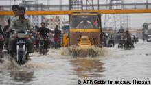 Commuters cross a flooded street during heavy monsoon rains in Karachi on July 30, 2019. (Photo by ASIF HASSAN / AFP) (Photo credit should read ASIF HASSAN/AFP/Getty Images)