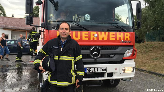 Tobias Schaarschmidt stands in front of a fire truck at his fire station in St. Katharinen, Rhineland-Palatinate