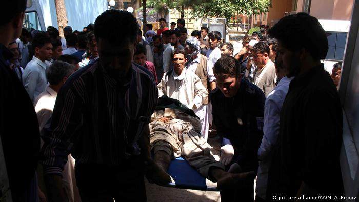 A wounded person is being carried after a major roadside landmine blast on July 31, 2019 in Herat, Afghanistan