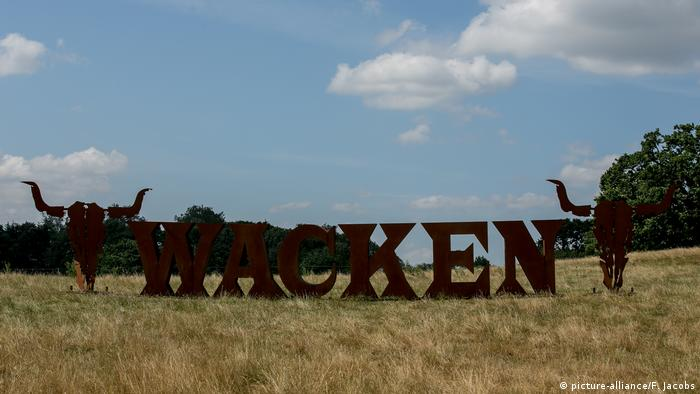 Rusty letters spelling Wacken, framed by cow skulls, on a meadow (Foto: picture-alliance/F. Jacobs).