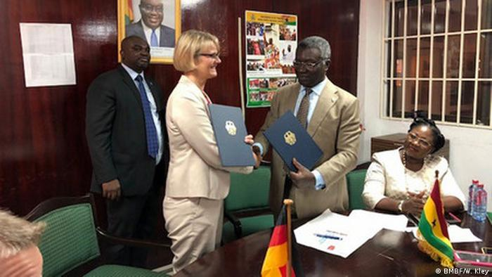 Minister Karliczek shakes hands and exchanges files with a Ghanaian official