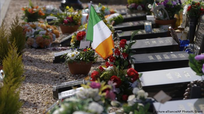 An Irish national flag is placed near a grave in the Irish Republican plot at Milltown cemetery off the largely Nationalist Falls Road area in Belfast, Northern Ireland, Friday, March 24, 2017. (picture-alliance/AP Photo/A. Grant)