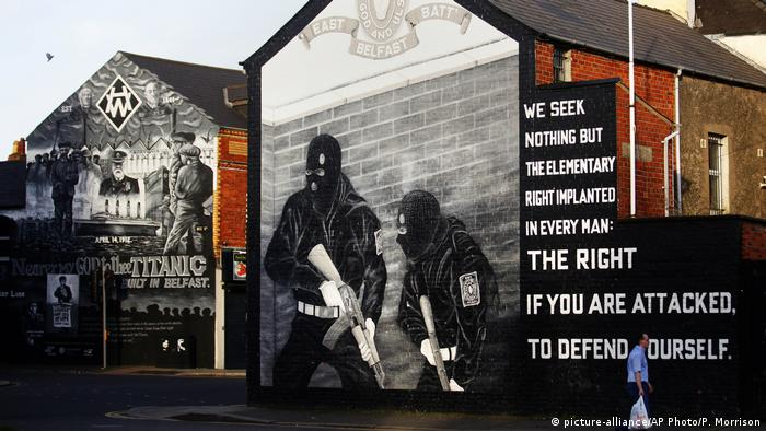 A man walks past Loyalist paramilitary mural in the Shankill Road a predominantly loyalist area in Belfast, Northern Ireland