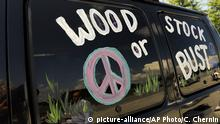 FILE - This Aug. 14, 2009 file photo shows a van decorated with Woodstock or Bust at the original Woodstock Festival site in Bethel, N.Y. Woodstock 50 is officially cancelled. Organizers announced Wednesday, July 31, 2019 that the troubled festival that hit a series of setbacks in the last four months won't take place next month. The three-day festival was originally scheduled for Aug. 16-18, but holdups included permit denials and the loss of a financial partner and a production company.(AP Photo/Stephen Chernin, File)  