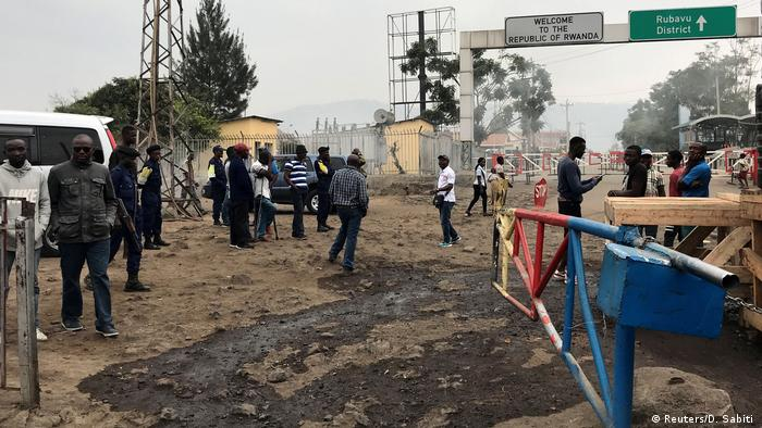 Congolese customs agents gather at the gate barriers at the border crossing point with Rwanda following its closure over ebola threat in Goma