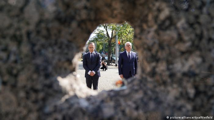 Heiko Maas and Jacek Czaputowicz seen through a bullet hole in a wall at the 75th anniversary event for the Warsaw uprising