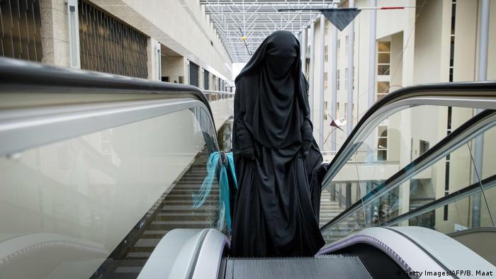 Niederlande Den Haag | Frau mit Burka auf Rolltreppe