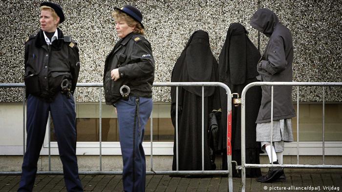 Женщины-полицейские и женщины в черной религиозной одежде на улице в Амстердаме