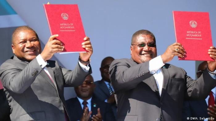 Ossufo Momade (right) and President Filipe Nyusi waving peace documents (DW/A. Sebastião)