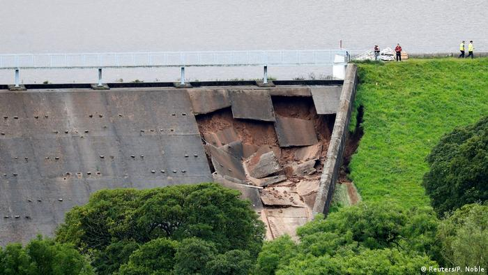 A damaged dam is seen after a nearby reservoir was affected by flooding, in Whaley Bridge