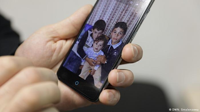 Хасан показывает фотографию своих детей
