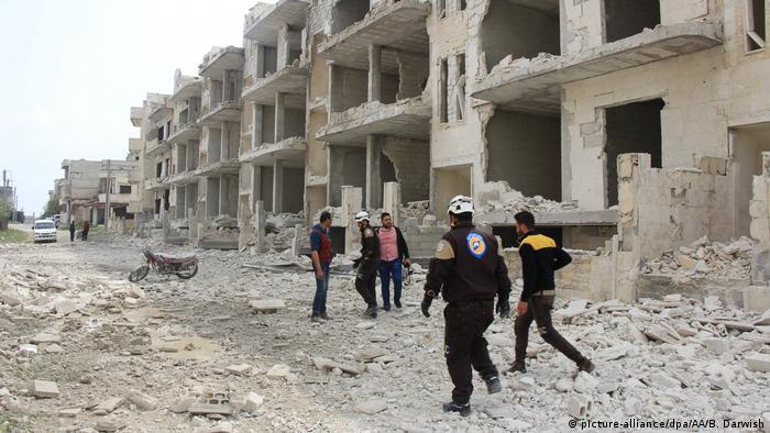 Policiais e outros homens caminham por cidade do Oriente Médio em ruínas