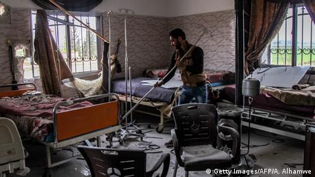 A man clears rubble at a damaged hospital ward in Saraqib. Amer Alhamwe / AFP
