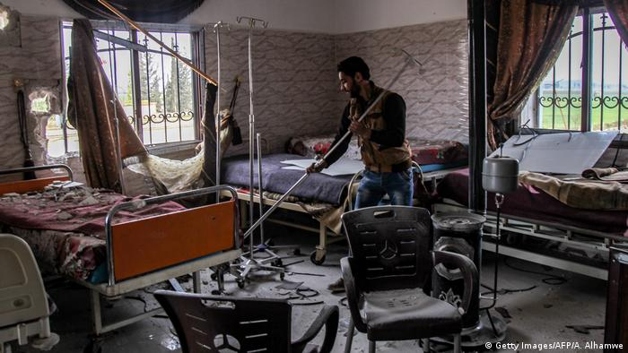 A man clears rubble at a damaged hospital ward in Saraqib. Amer Alhamwe / AFP