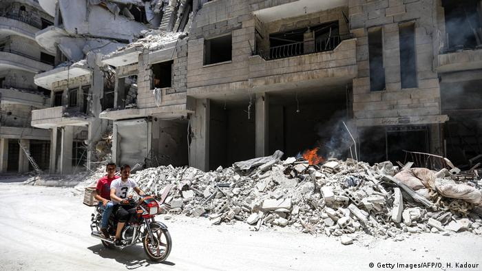 Men on a motorbike ride past a destroyed hospital in Idlib