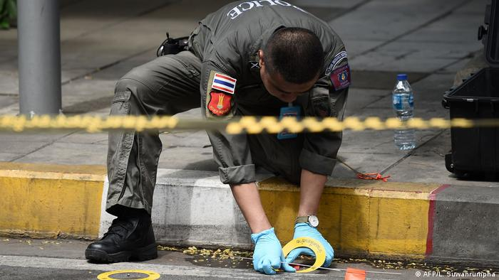 Thai police officer recovers small explosive device (AFP/L. Suwanrumpha)