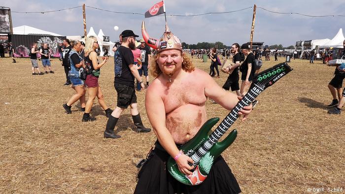 Mann mit Wikingerhelm und nacktem Oberkörper hält eine aufblasbare Gitarre