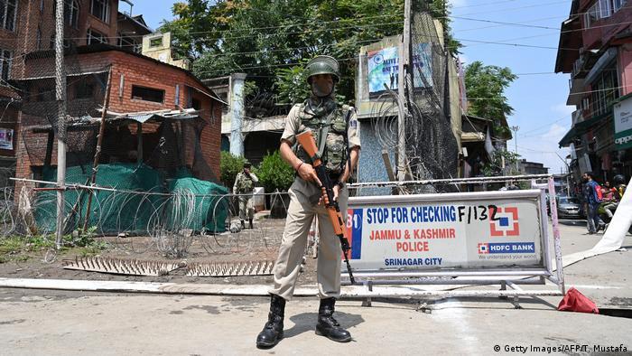 Control militar en Srinagar, frente a un aviso de la Policía de Jammu y Cachemira. (Getty Images/AFP/T. Mustafa)