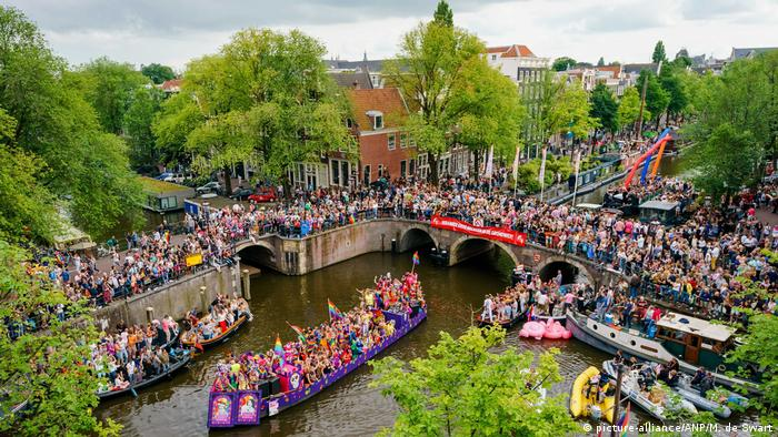 Thousands of people line the canals in Amsterdam