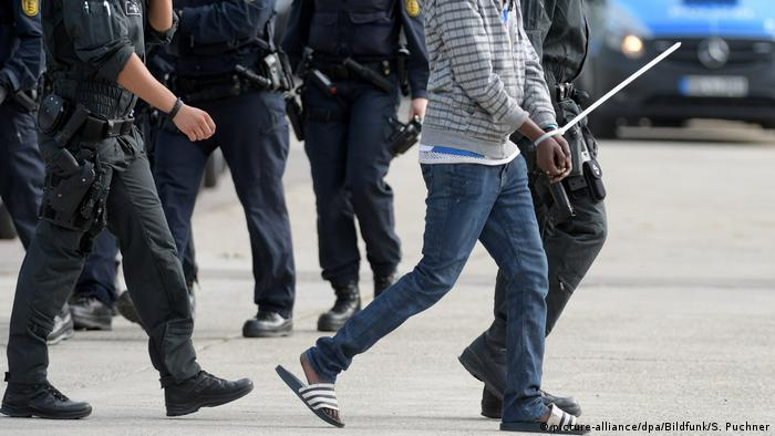 Police accompany an asylum seeker to a flight
