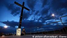 03.08.2019, Mexiko, Juarez: Eine Frau sitzt neben einem Schild mitder Aufschrift No more Guns, make Love nachdem ein Schütze in einem Einkaufszentrum in El Paso, im US-Bundesstaat Texas, mindestens 20 Menschen getötet und mindestens 26 weitere verletzt hatte. Es gibt Hinweise, dass es sich um ein Hassverbrechen handeln könnte. Foto: Christian Chavez/AP/dpa +++ dpa-Bildfunk +++