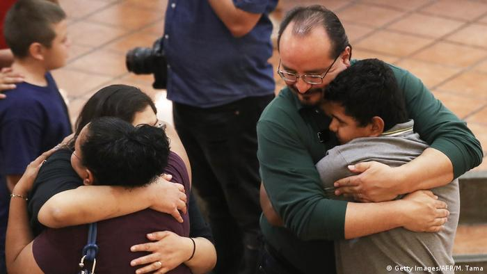 People hug at a vigil for the El Paso mass shooting