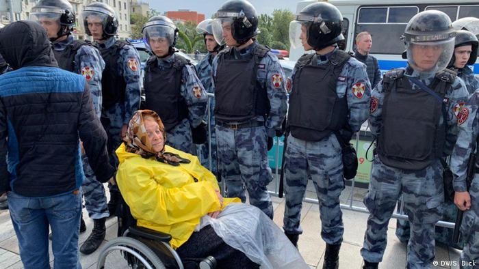 Пожилая женщина в кресле-каталке перед росгвардейцами