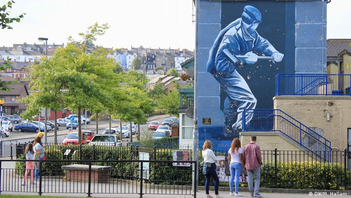 Londonderry - Derry, 02.08.2019+++Visitors look at memorials in Free Derry. In front of them is a large mural of a soldier with a sledgehammer breaking down a door. (DW/M. Hallam )