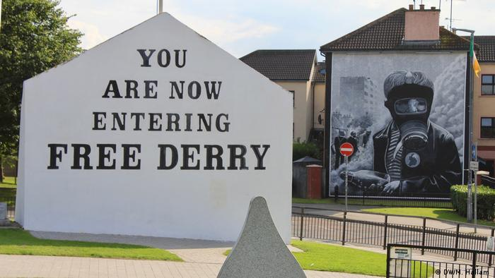 Londonderry - Derry, 02.08.2019+++A white wall with block black lettering: YOU ARE NOW ENTERING FREE DERRY. A mural to the right shows a young man in a gas mask, wearing a button with a map of Ireland, and holding a Molotov cocktail. The flag of the Republic of Ireland flies next to it. (DW/M. Hallam )