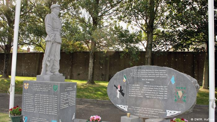 Londonderry - Derry, 02.08.2019+++A memorial at Creggan Parish Church graveyard to members of the Irish Republican Socialist Party and the Irish National Liberation army killed during fighting. A statue of a man in a balaclava, with a rifle at his side, stands below the flag of the Republic of Ireland. (DW/M. Hallam )