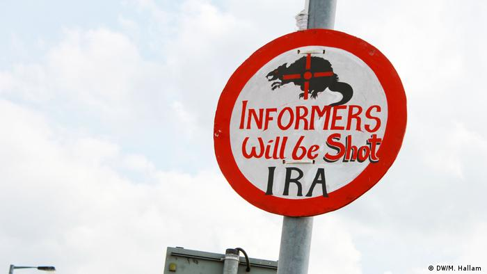 Derry, Londonderry: 02.08.2019+++An imitation road sign, erected near the site of investigative journalist Lyra McKee's murder on Creggan Estate in Derry, Londonderry. It reads: Informers will be shot, IRA. Above the lettering is a picture of a rat with a gun's crosshairs superimposed on top. (DW/M. Hallam )