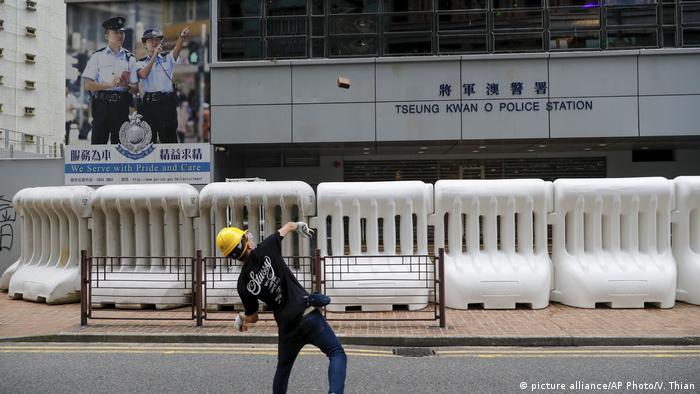 Hongkong Anti-Regierungsproteste - Demonstrant wirft einen Stein auf die Polizeistation (picture alliance/AP Photo/V. Thian)