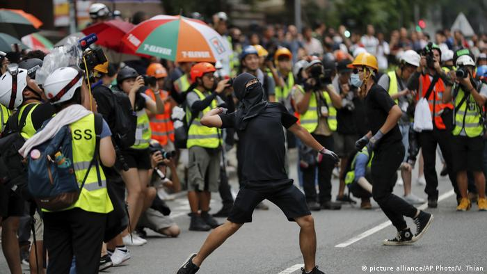 Journalists film as a protester throws a brick to the Tseung Kwan O police station during an anti-extradition bill protest in Hong Kong, Sunday, Aug. 4, 2019