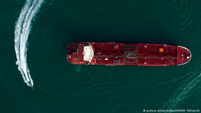 Visão aérea de um petroleiro no mar sendo circundado por um barco, que deixa um rastro na água